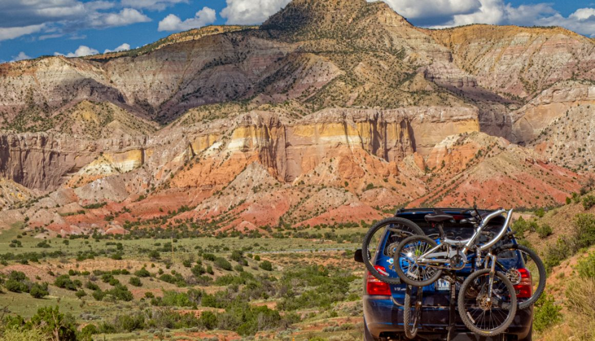 a car with bikes on the road with red yellow cliffs in the back