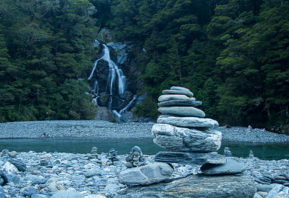 rock cairns in front of the waterfall