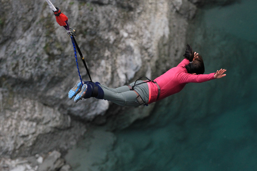 a woman bungy jumping over the water body