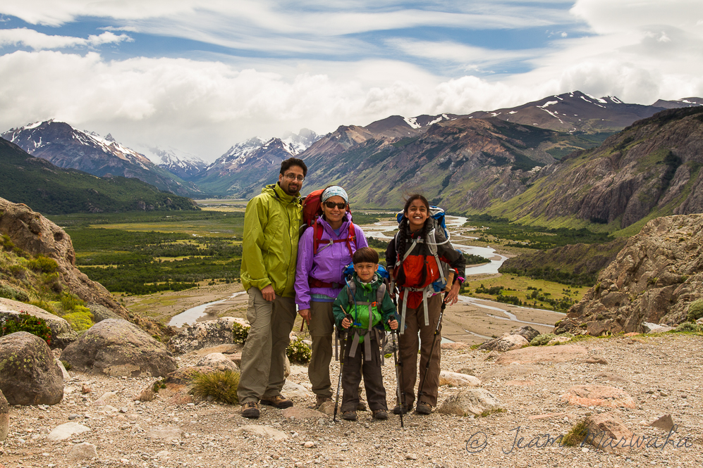family of backpackers posing for photo with mountains in the background