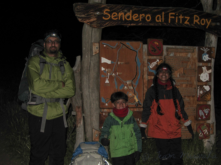 three hikers standing next to the sign