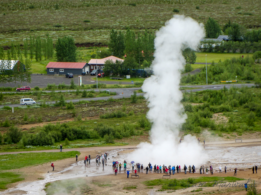 people watching eruption of a geyser