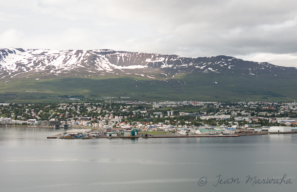 coastal town with a backdrop of snowy mountain