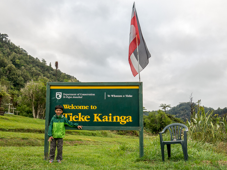 a boy standing in front of the sign and flag