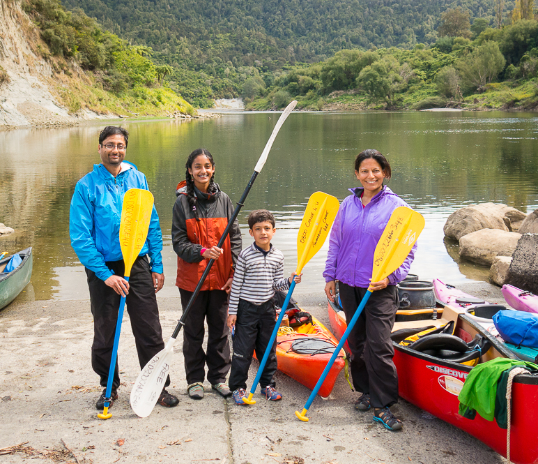 a family standing in front of the water body holding paddles in their hands