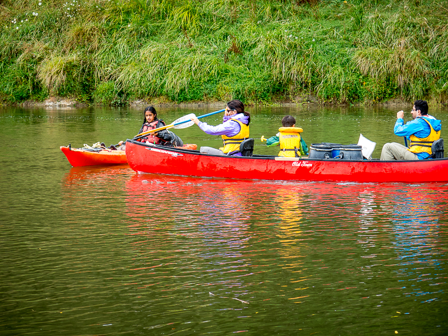 a family canoeing on a water body