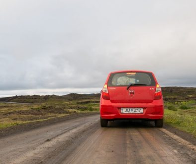 a red car on the dirt road in grass covered hills