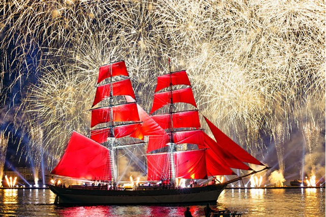 a boat with red sails and fireworks in the background