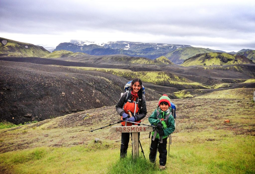 two kids with backpacks standing next to trail sign