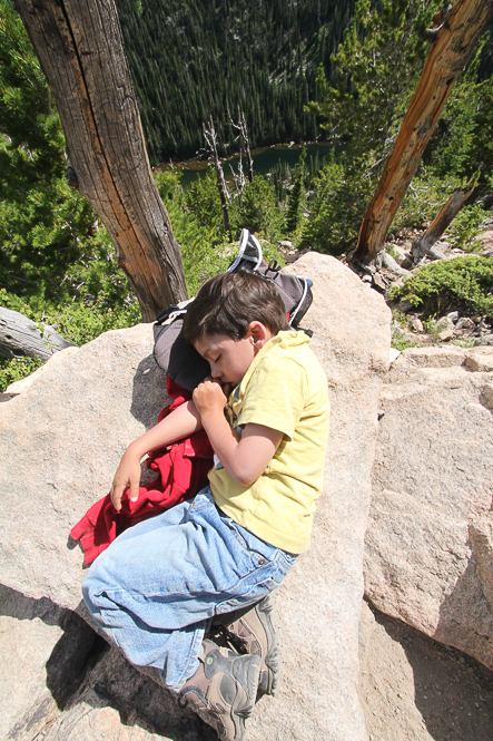 a child sleeping on a rock with thumb in his mouth