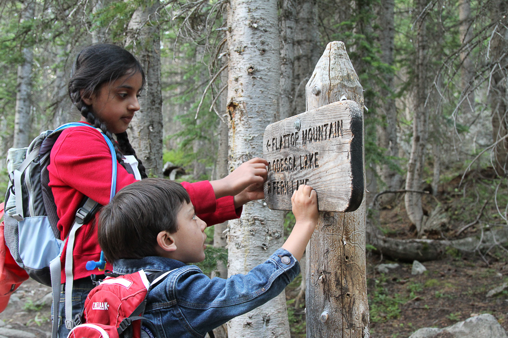 two children standing next to trail sign