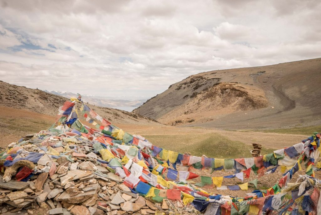 praying flags on top of the barren mountains