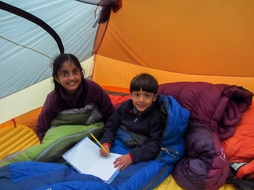 two kids sitting inside the tent in their sleeping bags