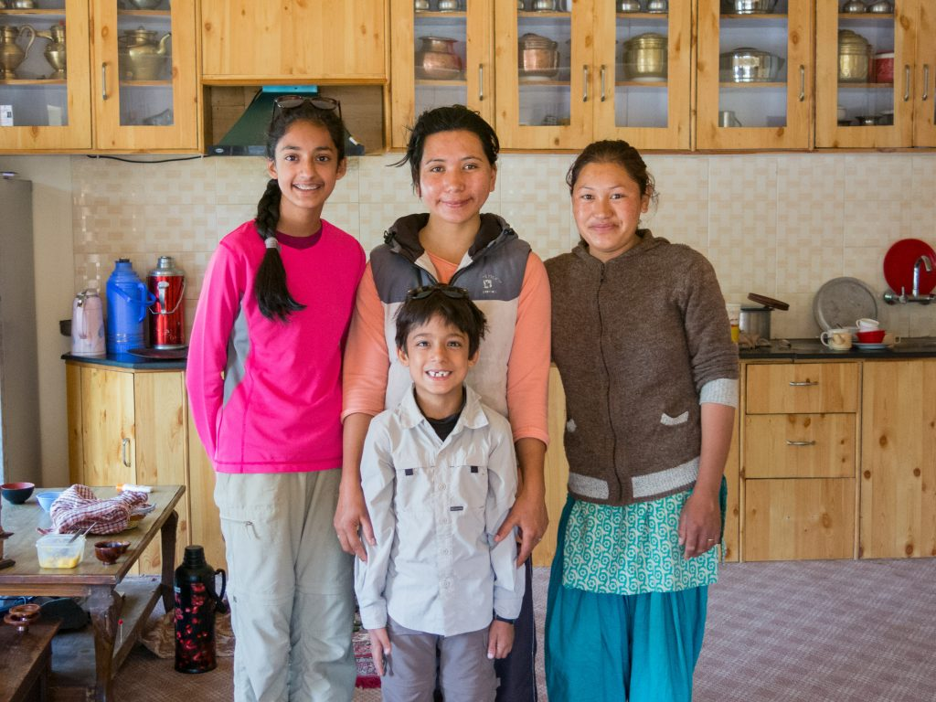 two children standing with two women in ladakhi kitchen