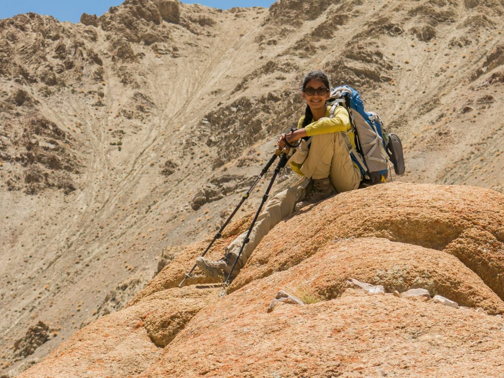 a girl with backpack and hiking pole sitting on a rock