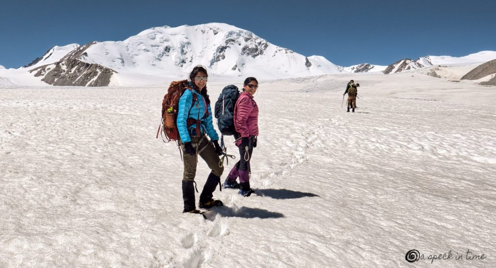 two women hiking in the snow over a glacier