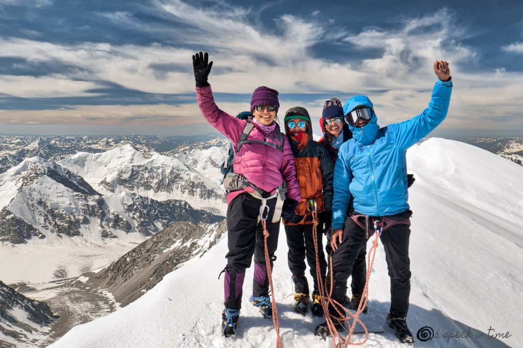 four climbers standing on top of the peak with glacier and mountain in the background