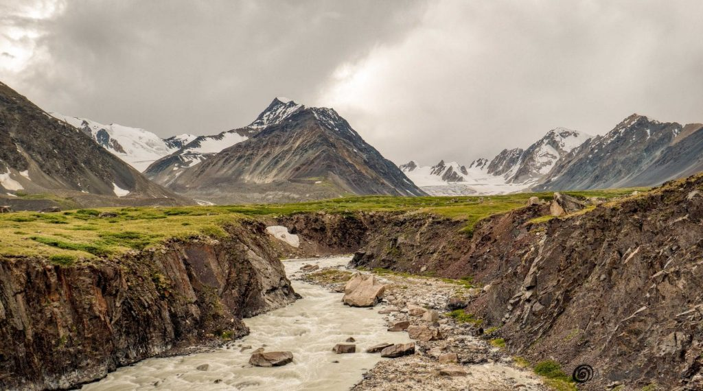 a river flowing through snow covered mountains in the backdrop