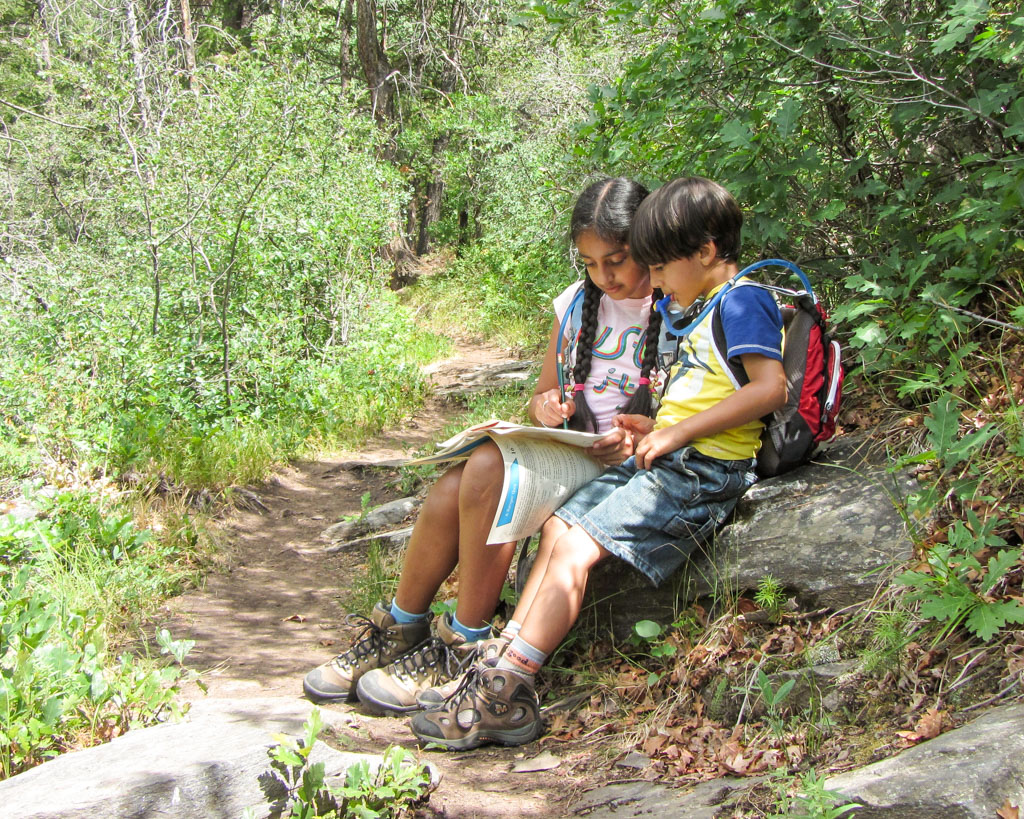 two children with backpacks sitting and writing