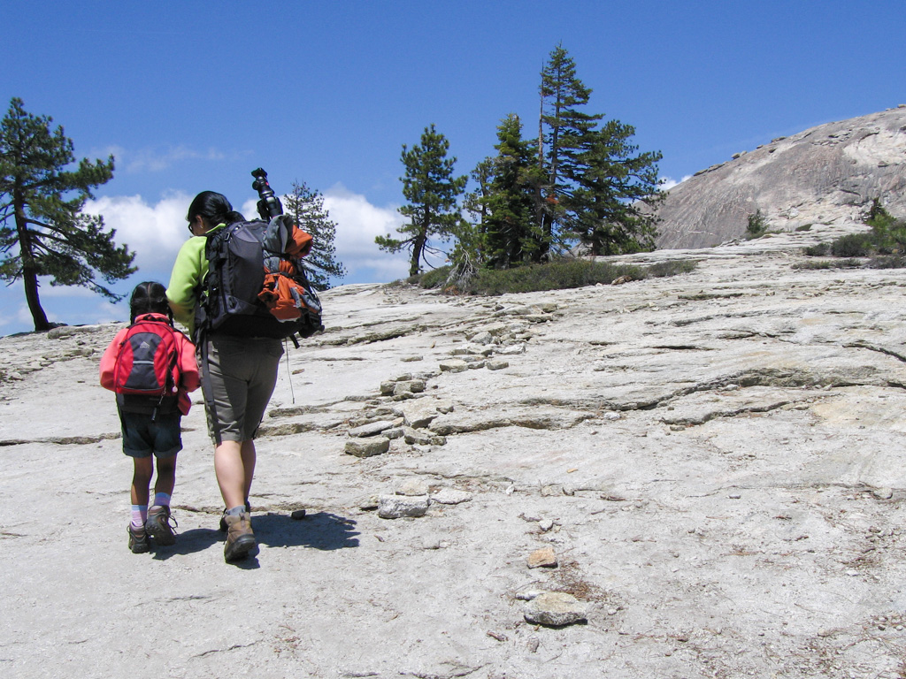 a woman and girl hiking up the boulder with backpacks