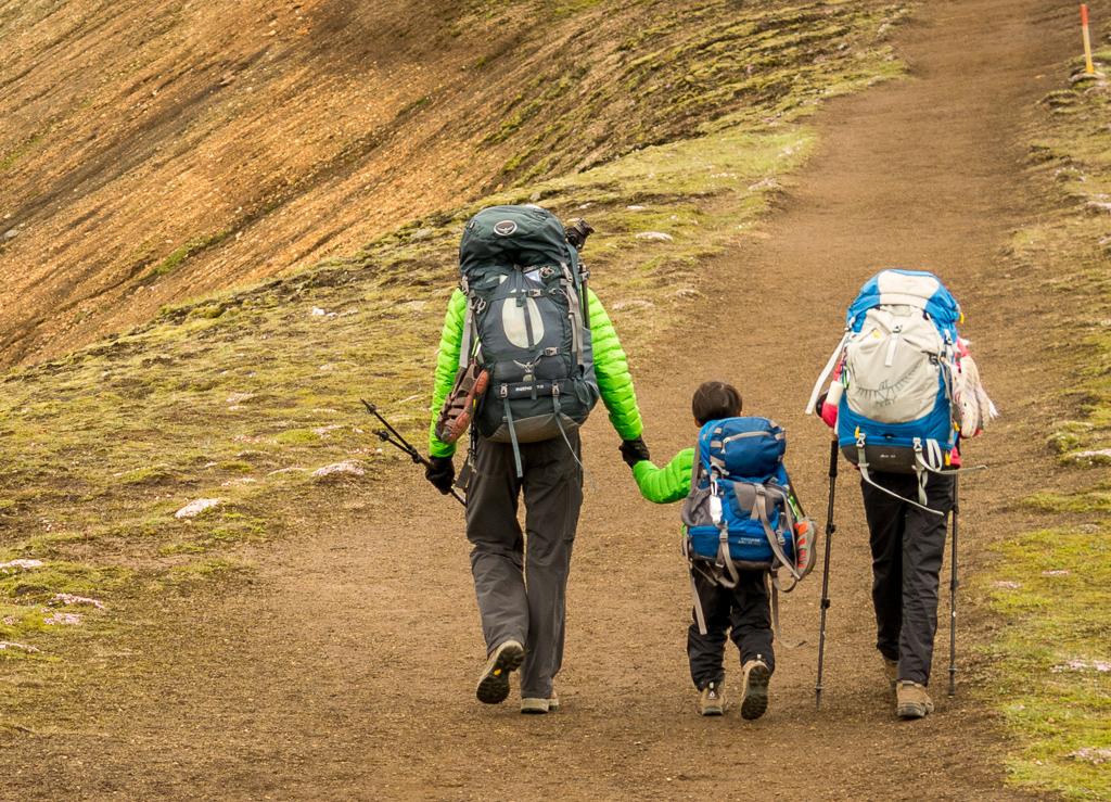 two kids with backpacks walking with an adult on the path