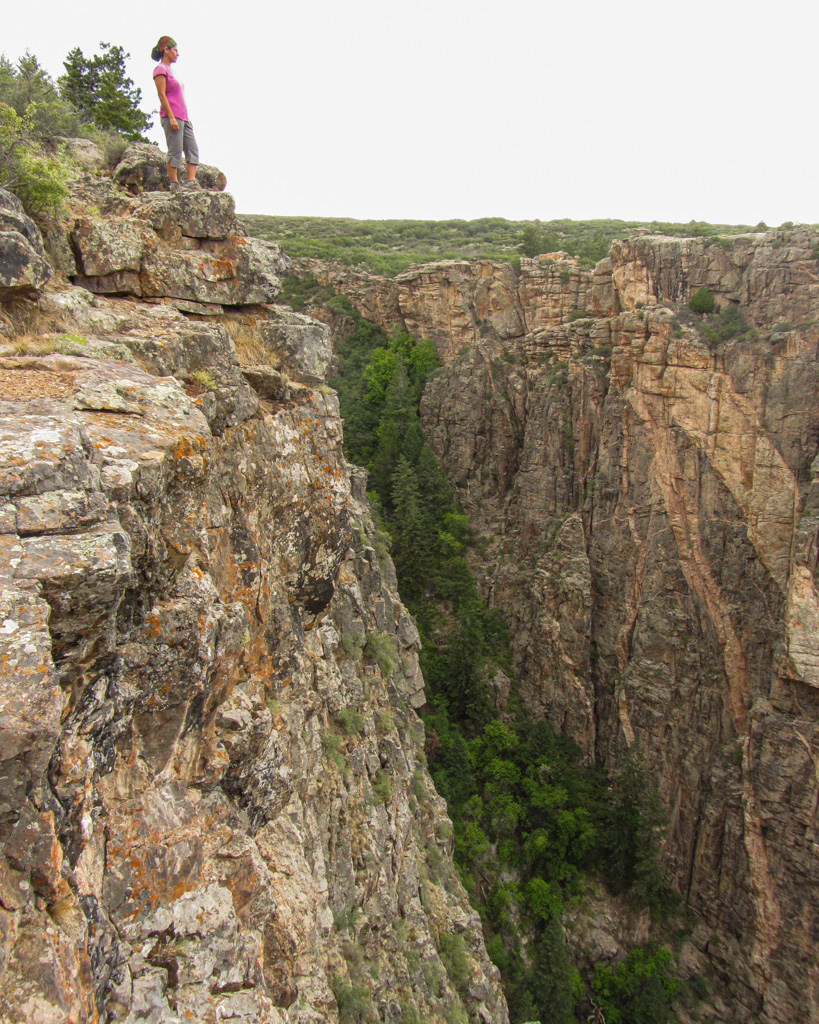 woman standing next to the cliff