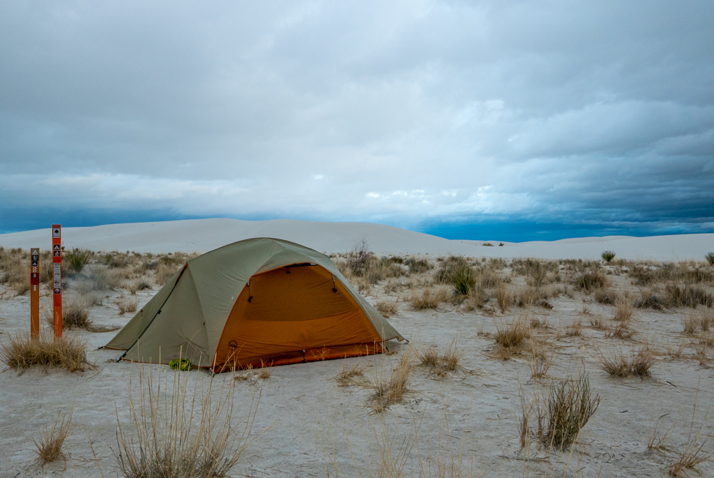 an orange tent on white sand with cloudy sky