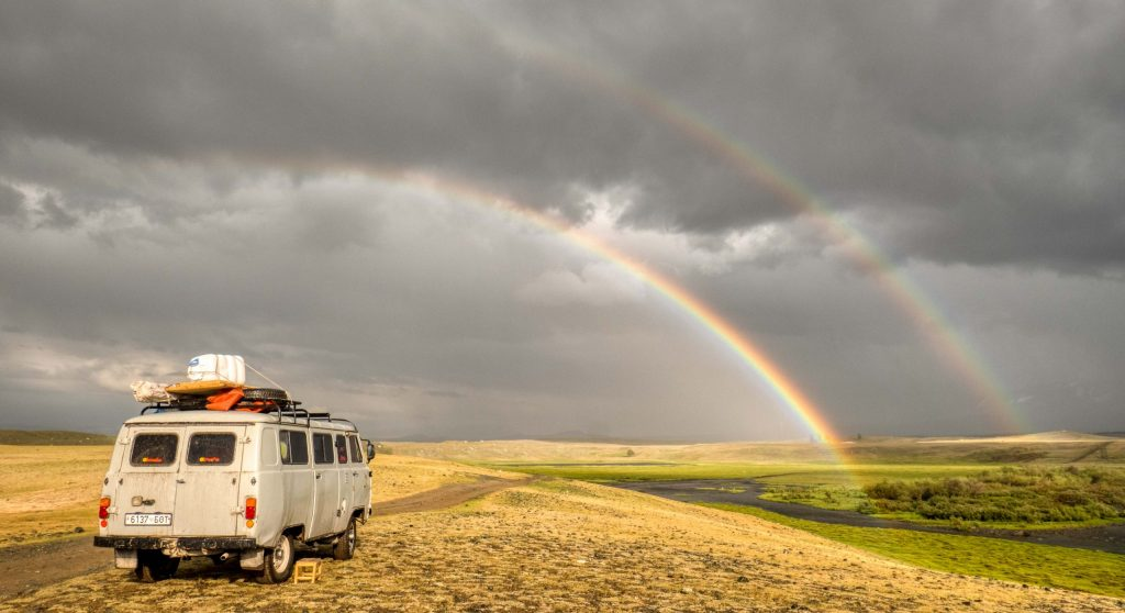 an old russian van in grassy field with double rainbow