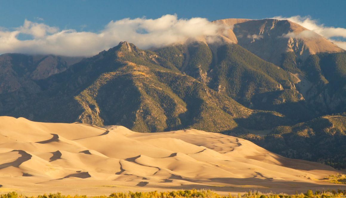 sand dunes with mountains in the back great sand dunes national park less crowded national parks