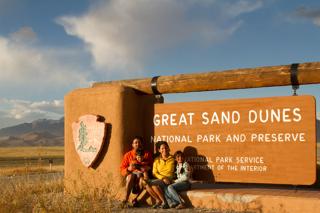 a family sitting in front of a board Great Sand Dunes National Park