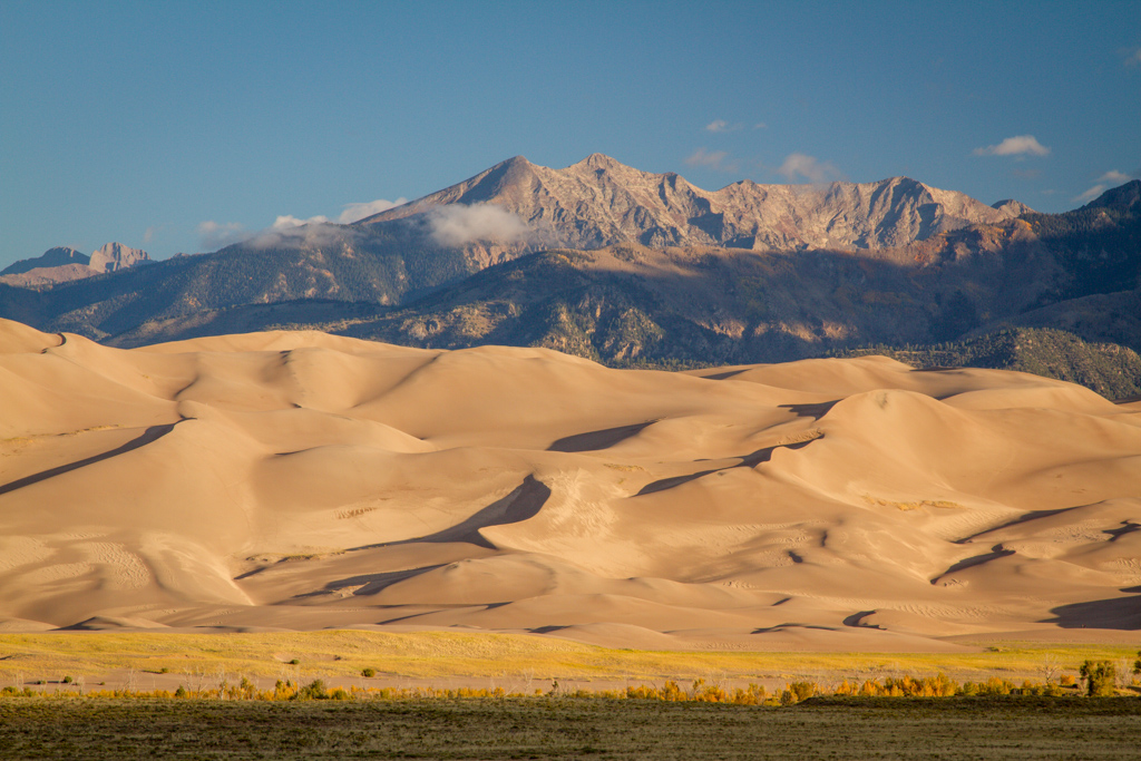 sand dunes with mountains in the back