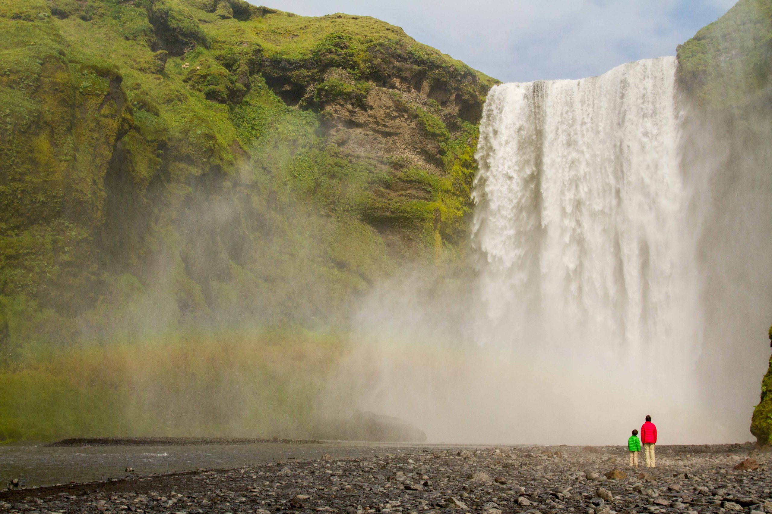 water falling over tall green cliff with rainbow and two kids standing in front of it