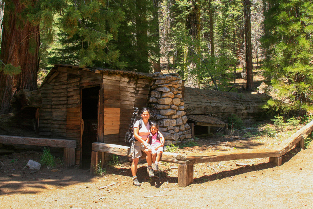 a woman and girl sitting next to a rustic cabin