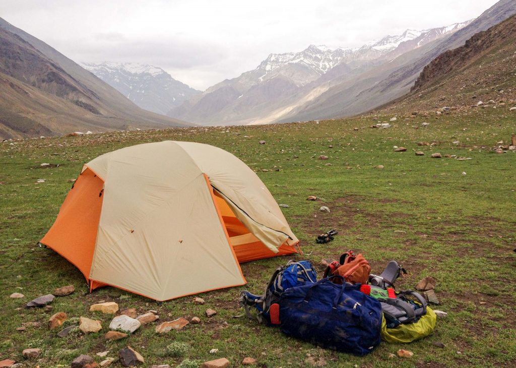 orange and beige tent in the mountains with backpacks