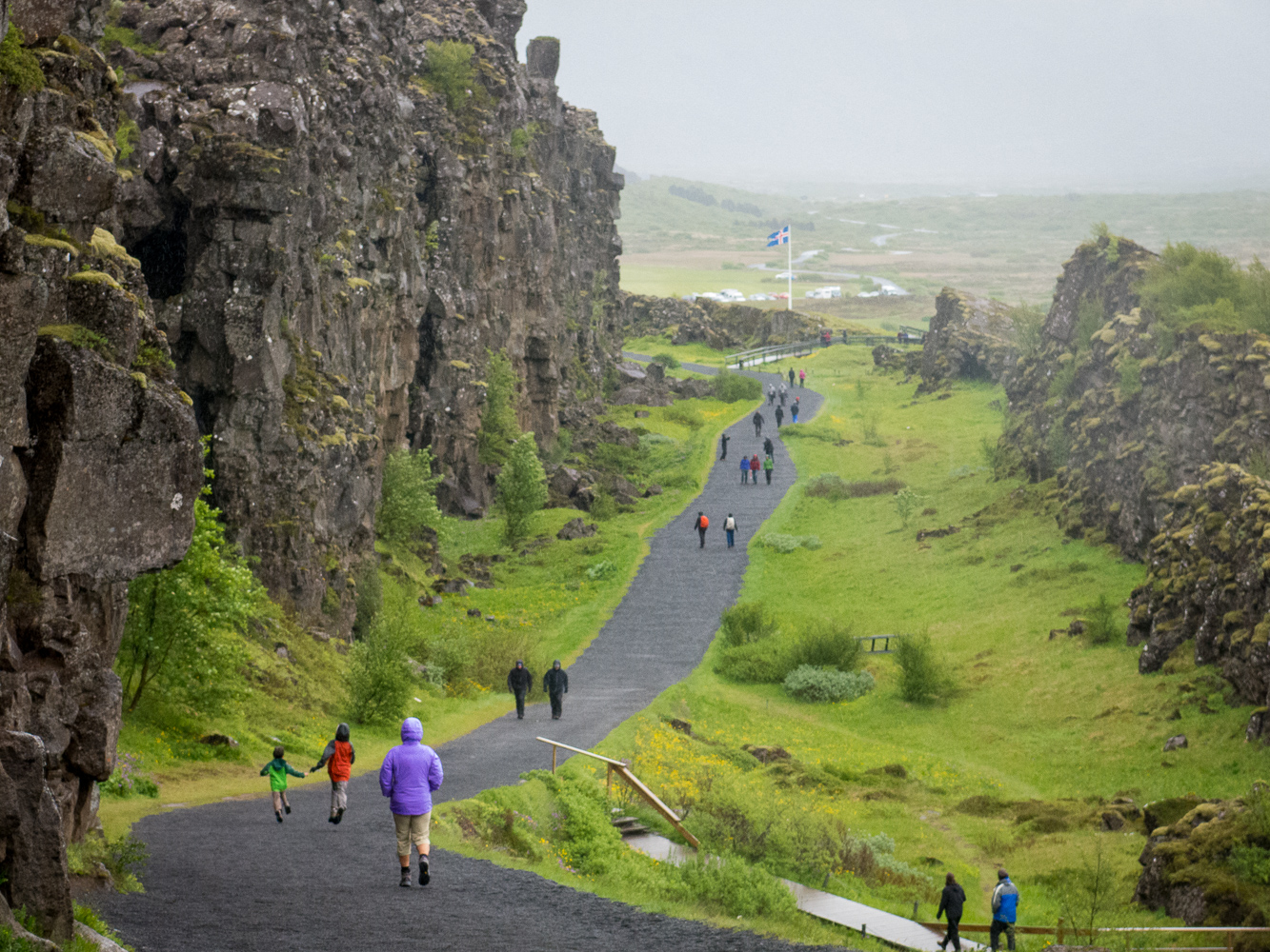 people walking on paved path in the mountains